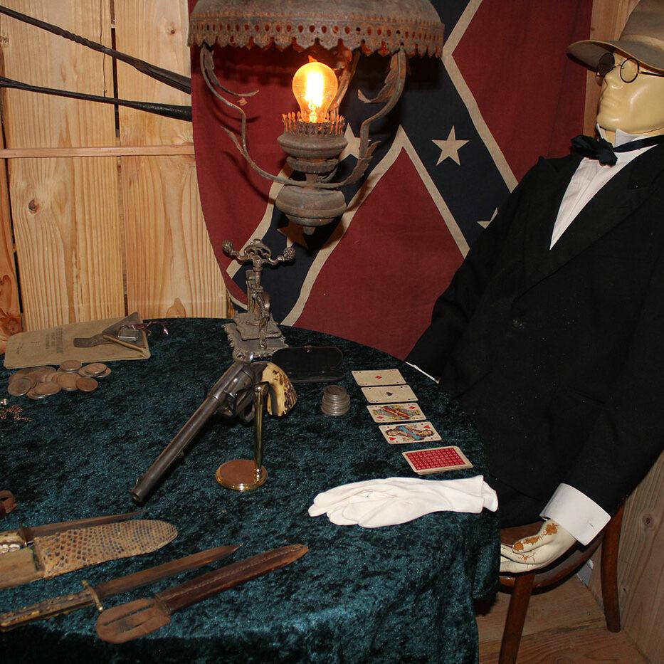 Kortspiller med kortpresser, sølvdollars og Bisley revolver